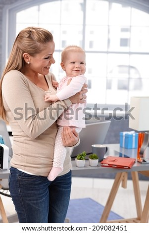 Mother holding baby girl in arms, standing at home, smiling.