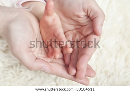 Mother holding baby hand in her hands