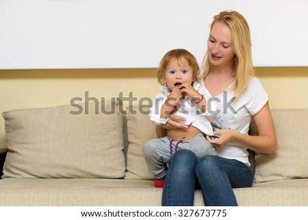 Mother holding baby in her arms. Child being surprised - stock photo