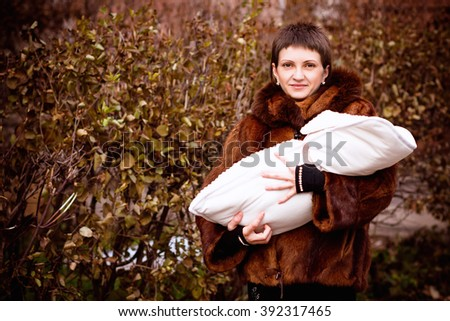 mother holding baby on arms, wrapped in a blanket. soft focus effect.