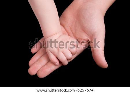 Mother holding baby's hand in her own isolated over black