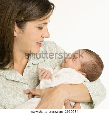 Mother holding baby smiling against white background.