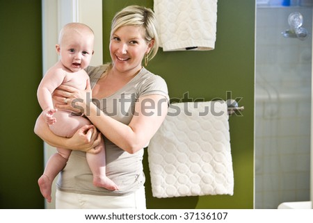 Mother holding bare seven month old baby in bathroom - stock photo