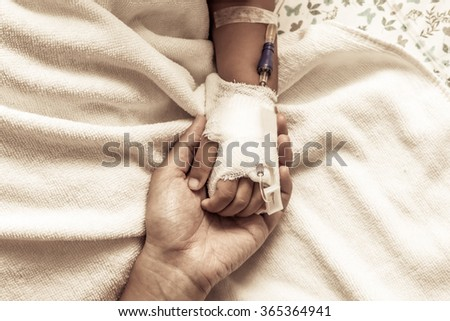 mother holding child's hand who have IV solution in the hospital in vintage color tone - stock photo