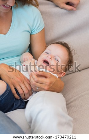 Mother holding cute baby boy at home