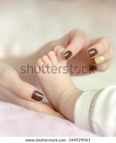 Mother holding cute baby's toe with fingers - stock photo