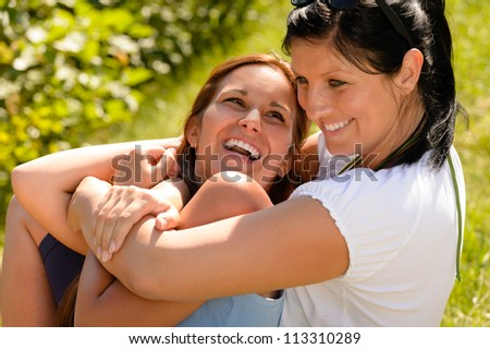 Mother holding daughter in her arms laughing outdoors relaxing teen