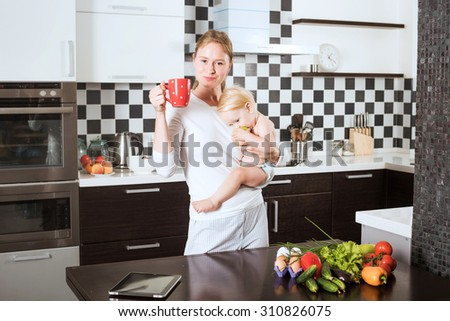 Mother Holding Daughter In Kitchen while cooking a meal of fresh vegetables and fruits. Mother and little daughter on kitchen holding an apple. Healthy food and healthy living concept