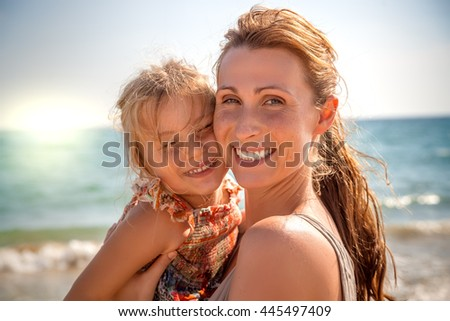 mother holding daughter laughing in camera - stock photo