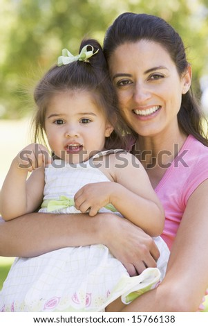 Mother holding daughter outdoors smiling - stock photo