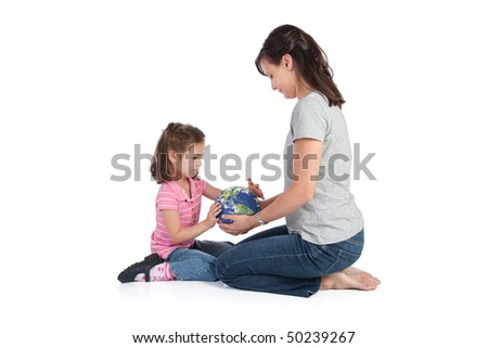 Mother holding globe of world while her daughter examines it. Teaching concept. Earth image courtesy of NASA. - stock photo