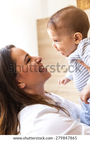 Mother holding her baby boy and playing. - stock photo