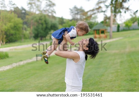 mother holding her baby in arms in meadow - stock photo