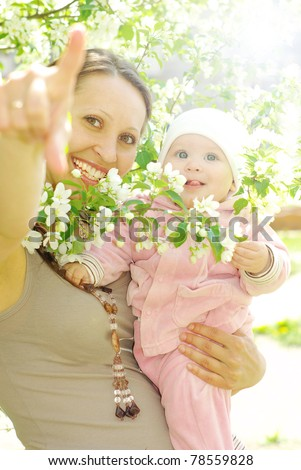 Mother holding her child against sunny leaves - stock photo