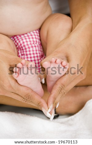 mother holding her child's feet on an isolated white background - stock photo