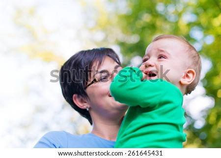 Mother holding her crying baby - stock photo