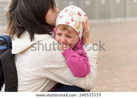 mother holding her crying daughter in arms - stock photo