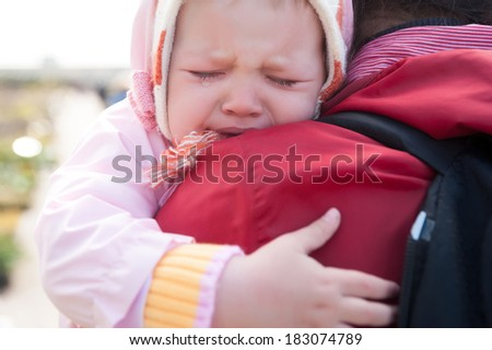 Mother holding her crying little baby girl - stock photo