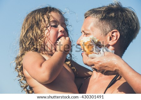 Mother holding her daughter against blue sky and sunshine while daughter is eating doughnut  - stock photo