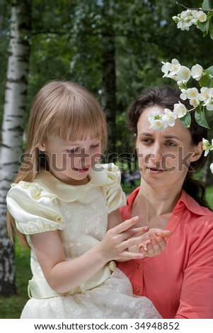 mother holding her daughter near jasmine flowers
