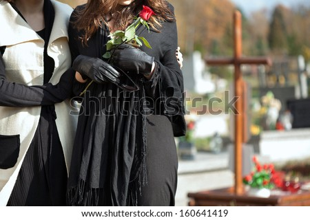 Mother holding her daughter standing above grave of family member - stock photo