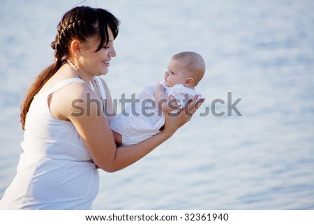 Mother holding her infant baby over sea