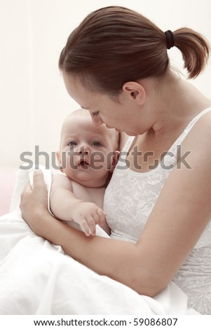 Mother holding her little cute baby girl. - stock photo