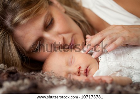 Mother holding her newborn baby, selective focus on baby - stock photo