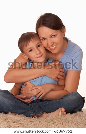 mother holding her smiling son on a white background