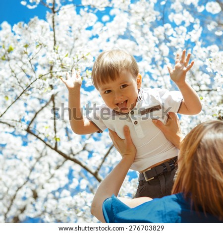 Mother holding her son boy toddler high in her arms, blooming white tree flowers and blue sky on the background, toddler smiling laughing showing his tongue being funny - stock photo