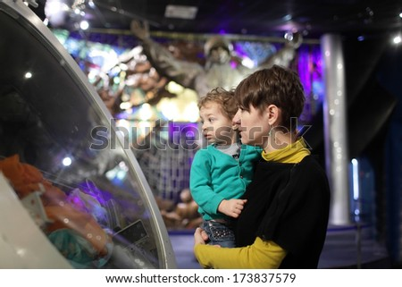 Mother holding her son in her arms in museum - stock photo