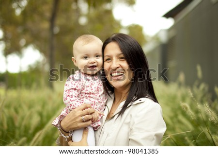Mother holding Little Baby in front of tall grass at the Park - stock photo