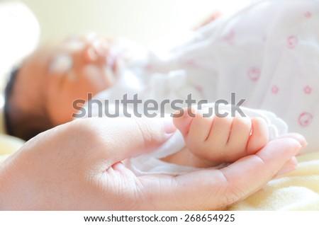 Mother holding newborn baby's hand - stock photo