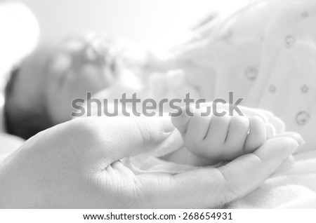 Mother holding newborn baby's hand - stock photo