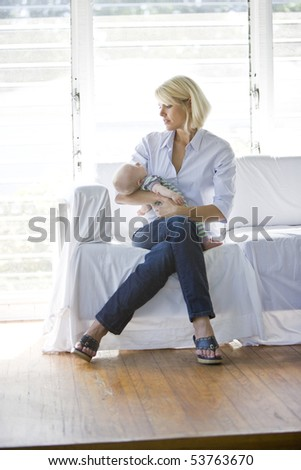 Mother holding sleeping 3 month old baby on sofa in sunny room at home