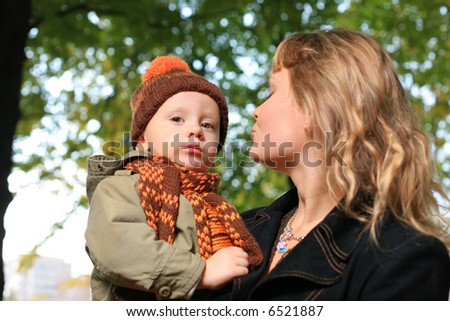 Mother holding small boy outdoors in park.