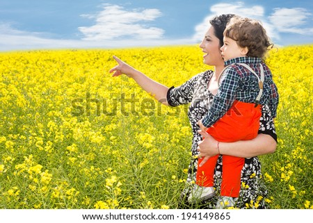 Mother holding son and poiting something to him in rapeseed  field - stock photo