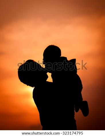 Mother holding son on the sunset sky background, Love family concept.