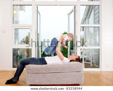 Mother holding son over head playing and having fun at home - stock photo