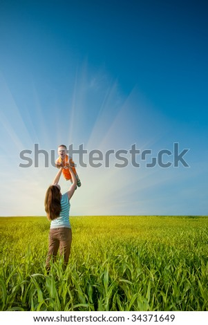 mother holding sun on the green field - stock photo