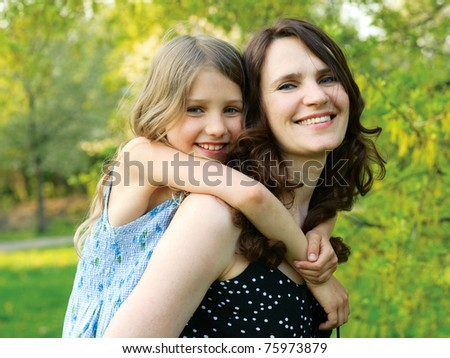 Mother holding the girl on the back - stock photo