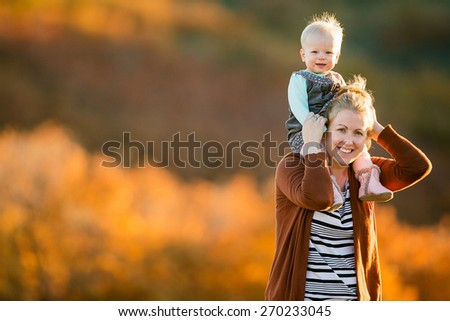 Mother holding toddler daughter on her shoulders - stock photo