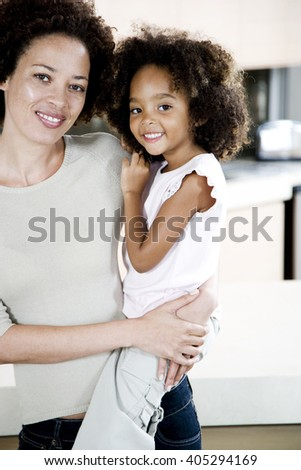 Mother holding young daughter at home, smiling - stock photo