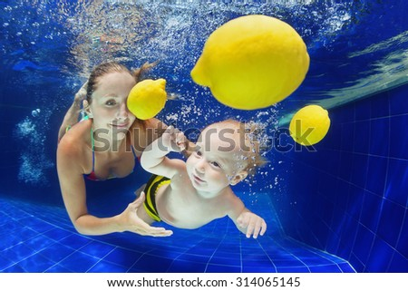Mother holds baby boy diving underwater with fun for yellow fruit in blue pool. Active lifestyle, child swimming lesson with parents, water sports activity on family summer vacation in tropical resort - stock photo