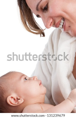 Mother holds baby in her arms looking at each other's eyes in tenderness