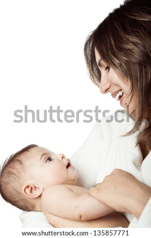 Mother holds baby in her arms looking at eachother eyes in tenderness