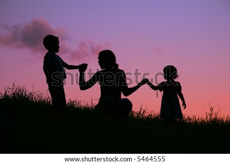 mother holds children for the hands on the sunset - stock photo