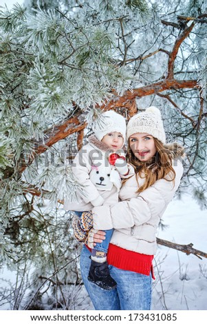 Mother holds daughter in her arms in the winter forest - stock photo