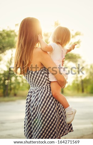 mother holds daughter on hands against the beautiful sunset - stock photo