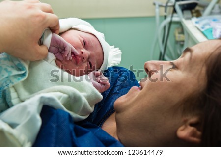 Mother holds her baby at the hospital right after delivery - stock photo